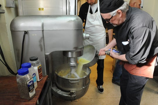 John Newkirk, program manager at Dorothy's Kitchen, adds ingredients to the mashed potatoes mix that will be served for Thanksgiving.