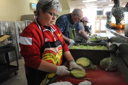 Volunteers cut lettuce and celery at Dorothy's Kitchen on Tuesday morning.
