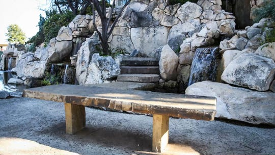 A bench near the waterfall feature behind the San Angelo Visitor Center along the Concho River.