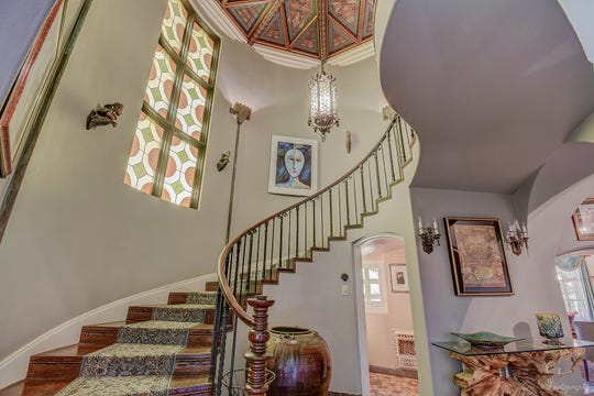 An exquisite curved staircase is located under the star patterned ceiling treatment.