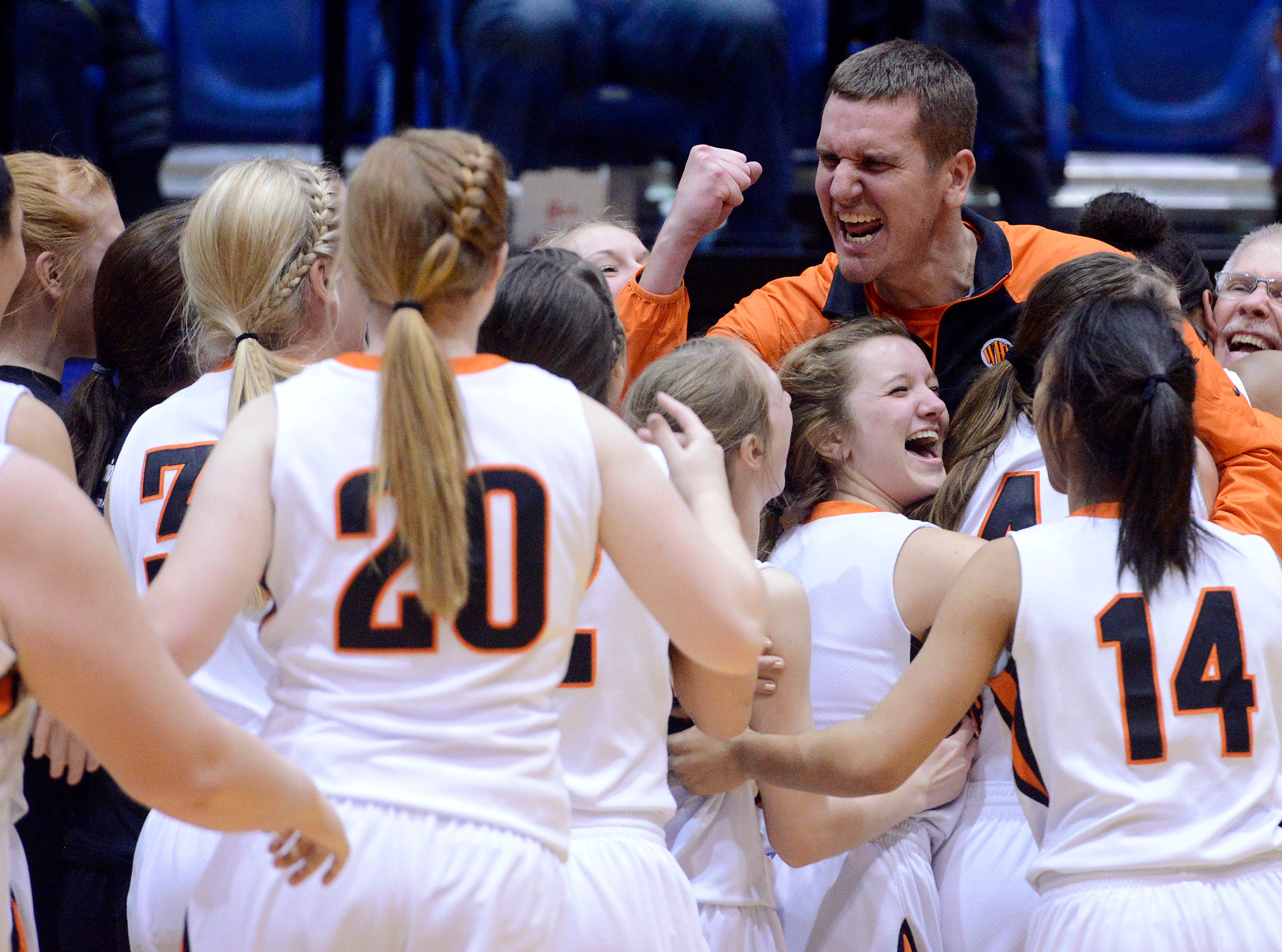 Washington head coach, Nate Malchow celebrates his team's 58-51 win over Mitchell Saturday at the Class AA girls high school basketball championship at Frost Arena in Brookings, March 15, 2014. 