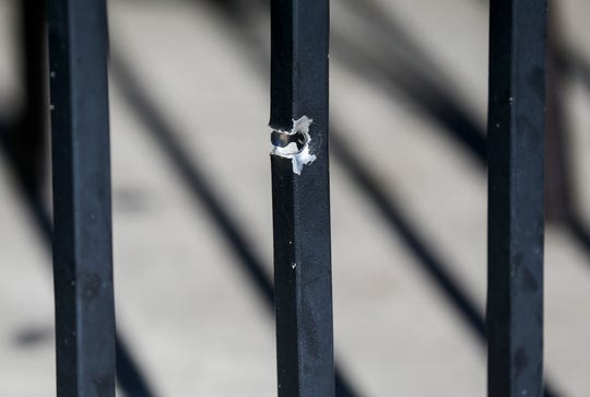 What appears to be a bullet hole can be seen going through a portion of the metal fencing at Tropical Liqueurs in downtown Springfield.