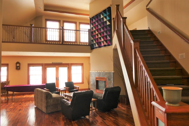 The great room is marked by the addition of a gas fireplace and a two-story wall that runs all the way to the loft.