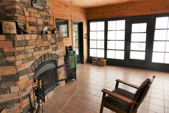 The three-season porch with the wood-burning stone fireplace provides the perfect respite for catching up on a book or relaxing.