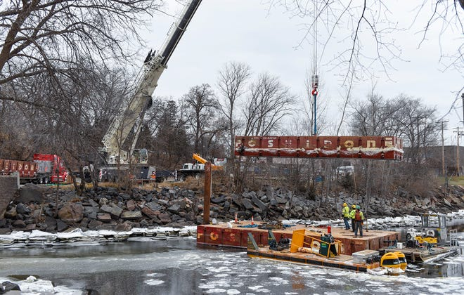 Workers from Veit USA and Landwehr Construction lift section of a construction barge from the Mississippi River Tuesday, Nov. 20, below the dam in Sartell.