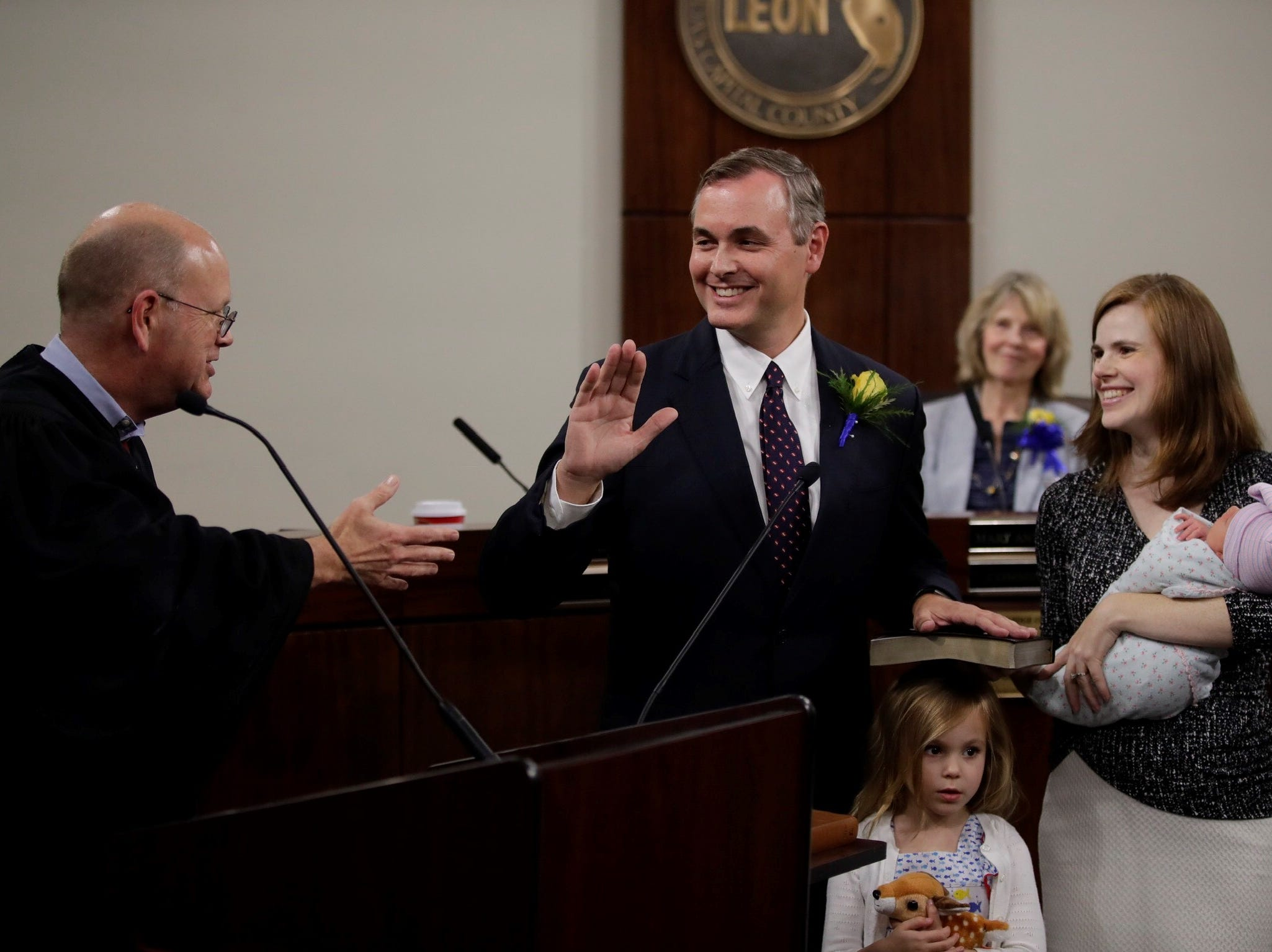 Rick Minor takes the oath of office as Leon County commissioner for District 3 on Tuesday, Nov. 20, 2018. Chief Circuit Judge Jonathan Sjostrom administered the oath of office as Minor's wife Jessica Lowe-Minor holds the family's Bible.