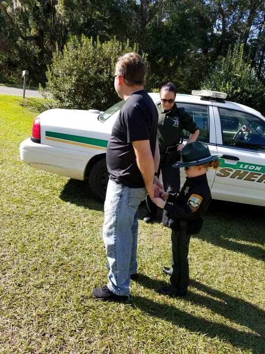 Jessalyn Younger-Gaskins (right), dressed up as her superhero Leon County Sheriff's Deputy Cecelia Crego (center) for Halloween, handcuffs her stepfather Andrew Souchik.