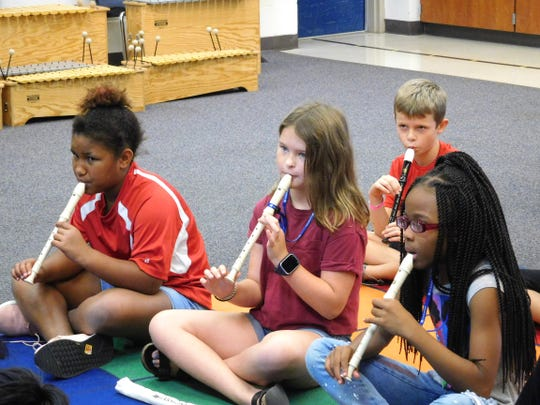 Preslee Donaldson (left) and her classmates play a song on the recorder.