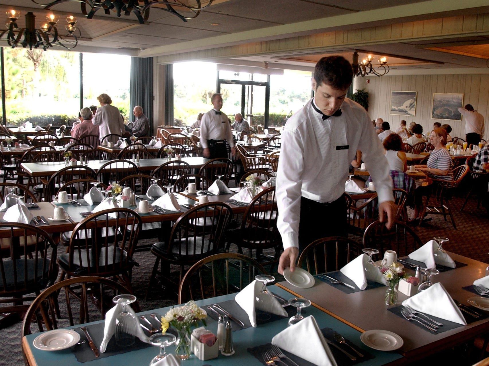 July 21, 2002 - Server Jon Kurtz sets up a table during Sunday brunch in the dining room at Dodger Pines Country Club. The Los Angeles Dodgers announced in earlier in the month that they were closing Dodger Pines Country Club Aug. 4, 2002, in advance of a pending sales contract with two Vero Beach developers who planned to build an 800-unit residential golf community on the property.