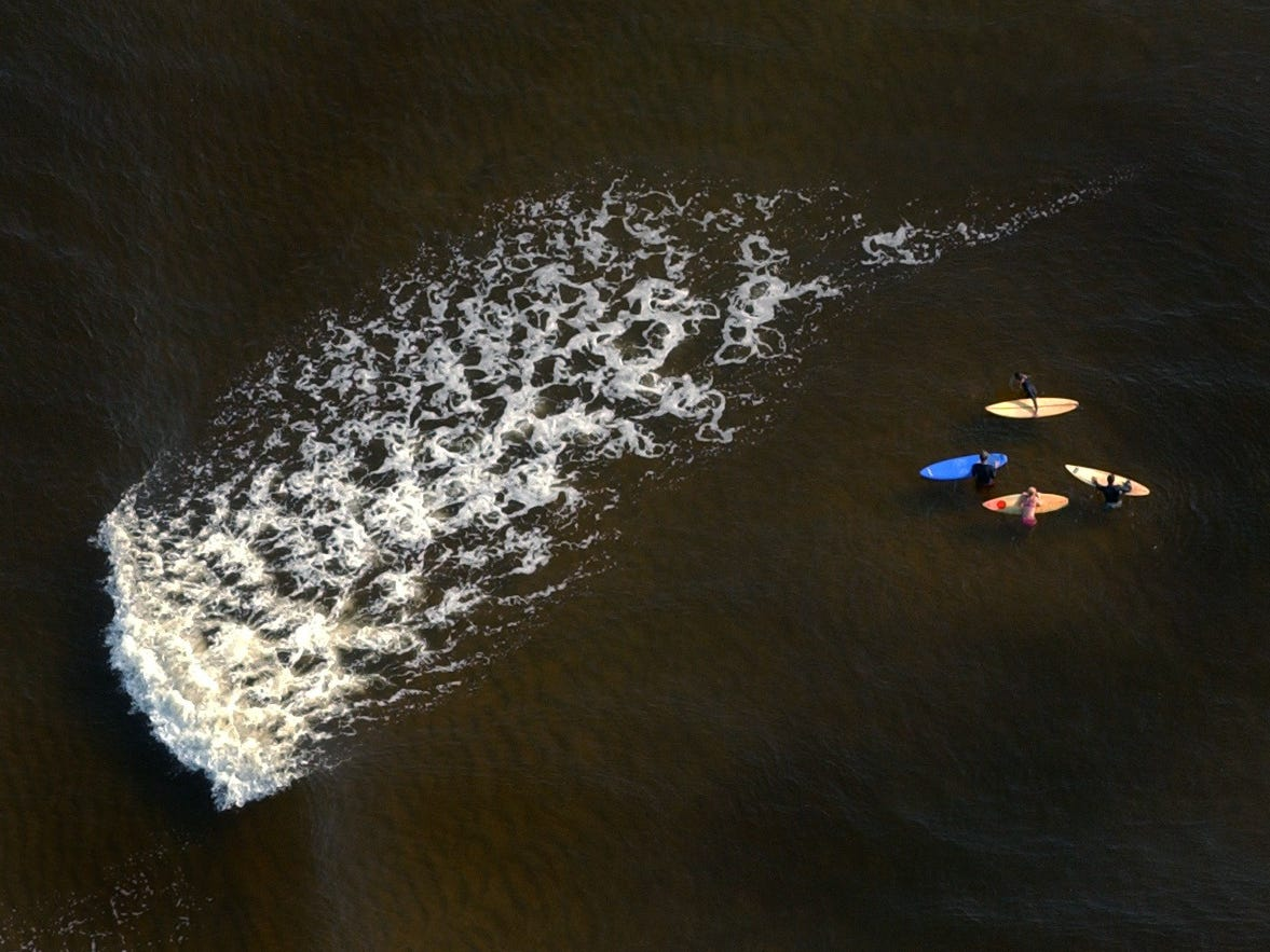July 18, 2002 - A group of four surfers watch a wave pass as they wait for the right one to hit while sitting in the shallow water at the Sebastian Inlet.