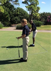 Tristan and Isaac, two residents of Samaritan Center for Young Boys & Families, enjoy lessons and a putting contest at the 50th Anniversary Golf Tournament.