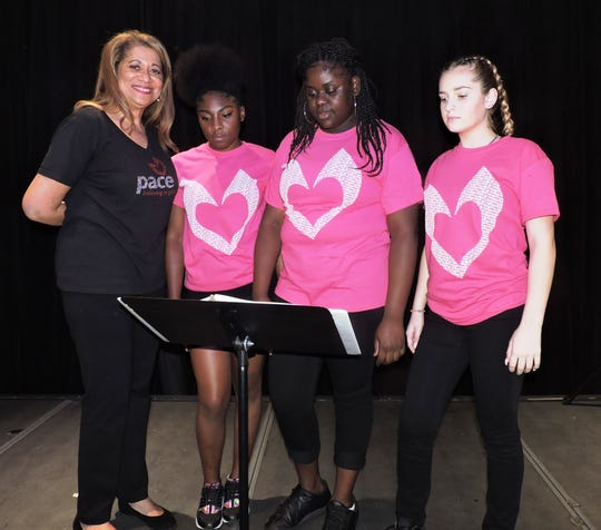 PACE Executive Director Vickie Coulter, left, helps poets Alysha, Cenijai and Sage practice their readings at the Sunrise Theatre Black Box in Fort Pierce.