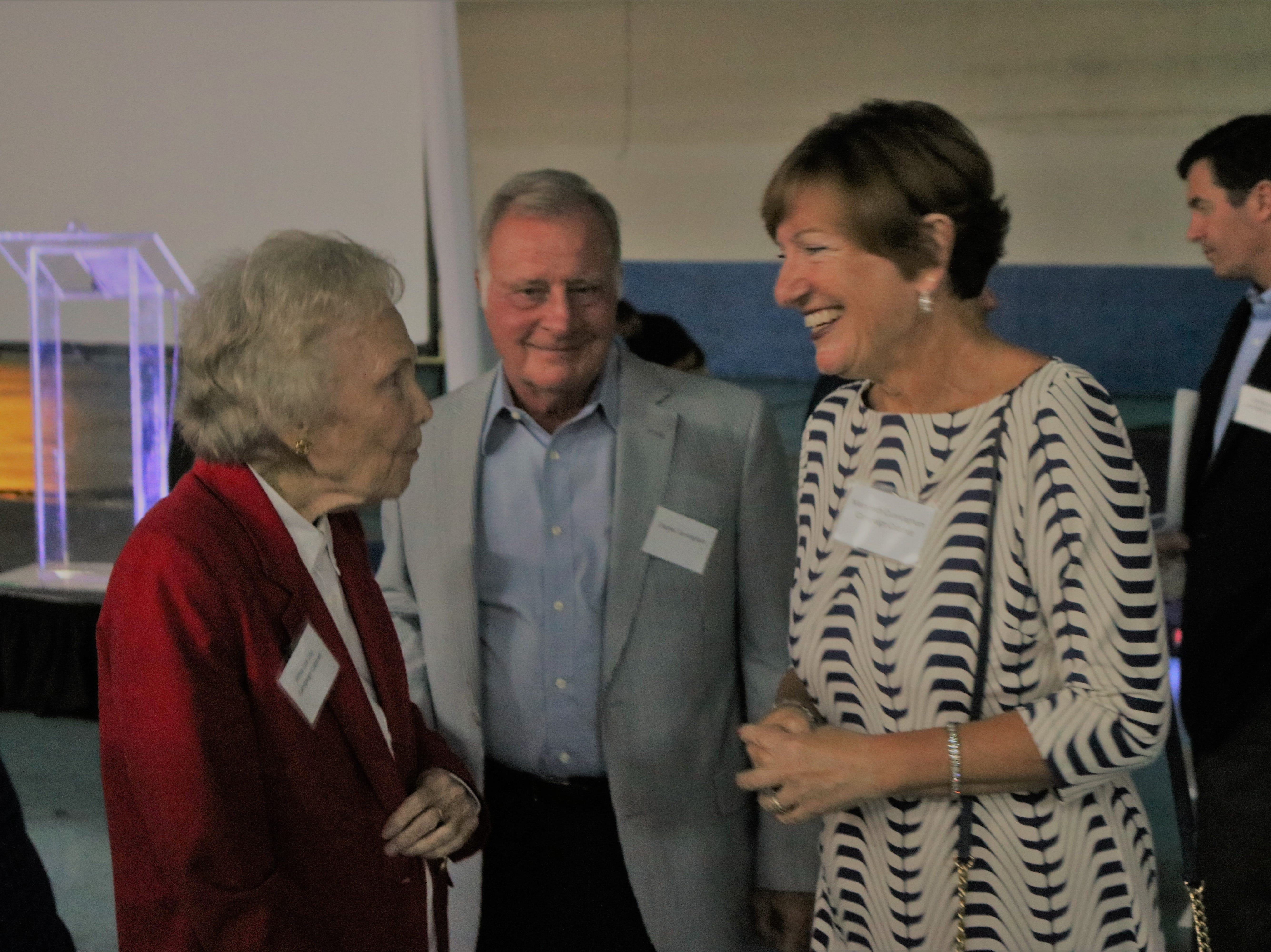 Alma Lee Loy, left, speaks with Chuck and MaryBeth Cunningham at United Against Poverty's Lifting Lives Out of Poverty Capital Campaign kick-off for Phase II.