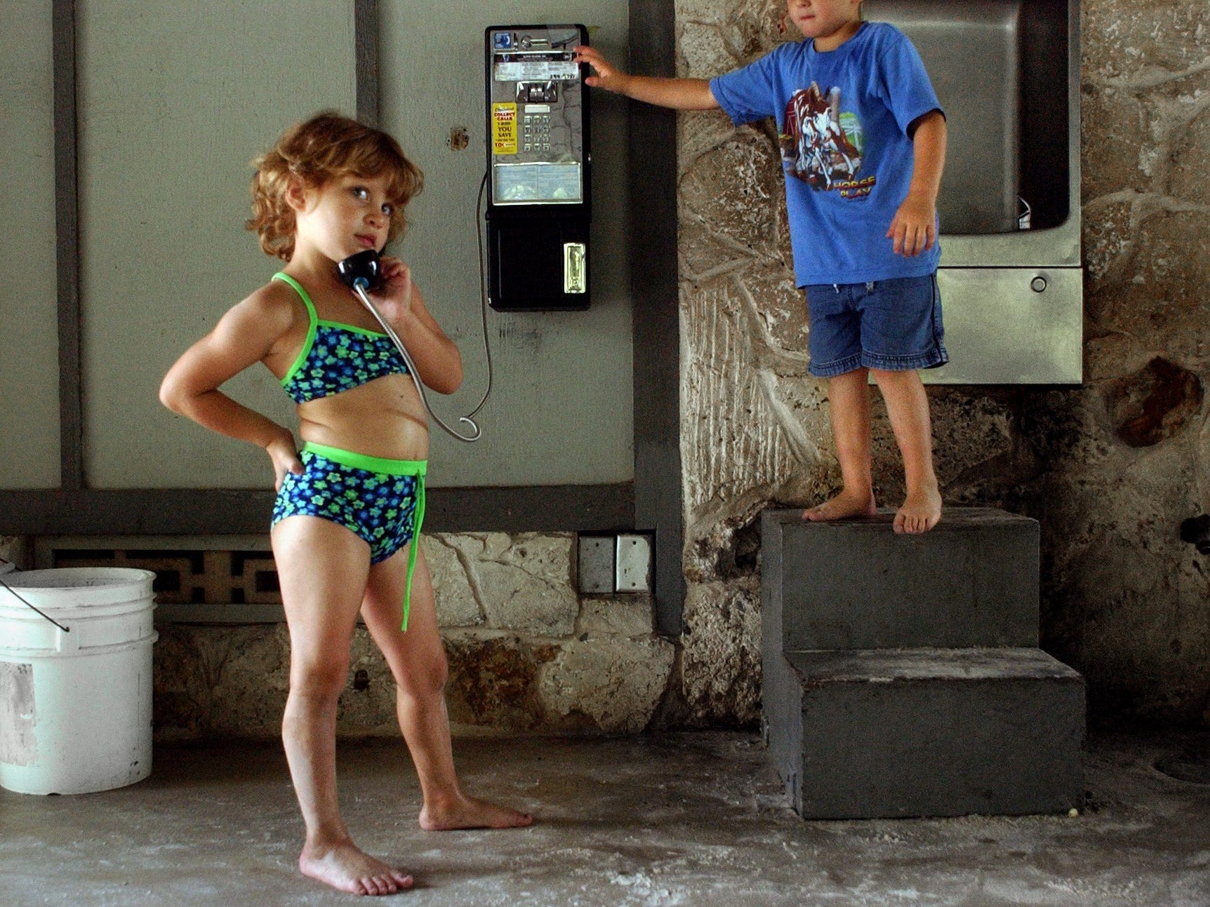 December, 2002 - Kylie Scent, 5, has an imaginary conversation on a broken pay phone while her cousin, Tyler Bales, 4, prepares to sabotage her call. The pair spent the afternoon with family at Charles Park in Vero Beach.