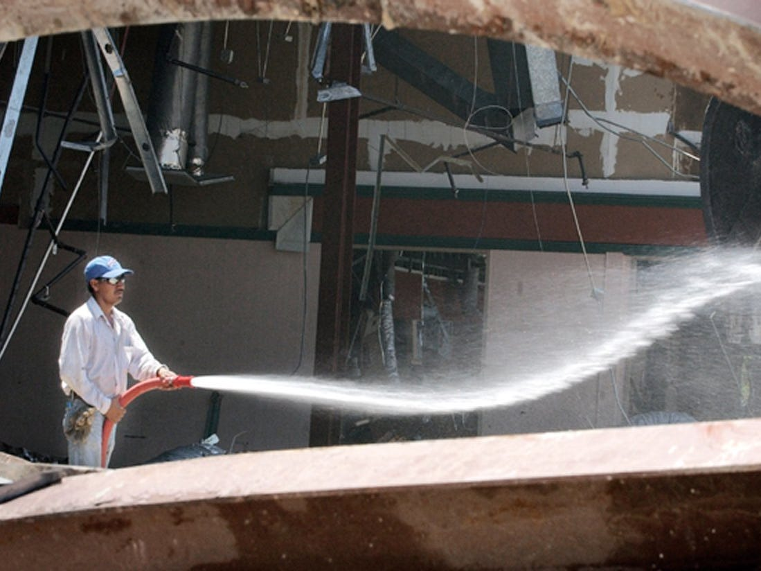 May 2, 2002 - Fermin Arriaga, of Cushing Demolition, sprays down the old Vero Mall to try to keep dust from flying while the building was being torn down. Paul Hanna Management Inc., of West Palm Beach, planned to reduce the 173,686-square-foot closed indoor mall into a 150,188-square-foot strip shopping center which includes a Publix Supermarket. The project was expected to be completed sometime in 2003.