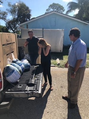 From left, Jeffrey Pedersen, executive director of Elev8Hope; Rina Shipiruk, founder of Elev8Hope; and Shaun Plymale, managing partner of Treasure Coast Legal. Shaun Plymale surprised Rina Shipiruk and Elev8Hope by donating a freezer full of turkeys.