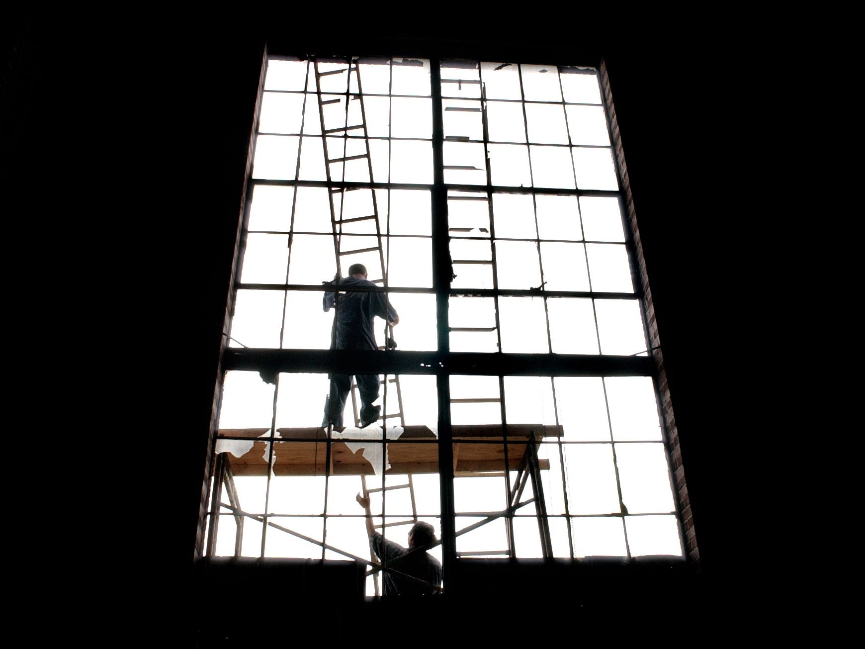 April 3, 2002 - Pete Kollas (top) and Jose Garcia, of BCI General Contractors in Virginia, begin to cover the windows of the Old Diesel Power Plant building. The crew was hired to pressure wash the building at 19th Place bordering the railroad tracks. Developers Phil Barth and Charles Block had plans to turn the electric plant and the old water plant into space for restaurants and retail businesses at the time.