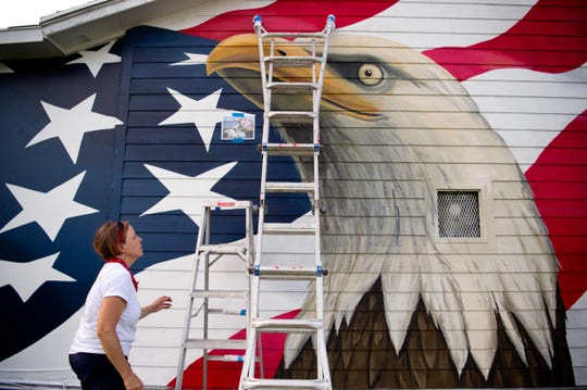 """Artist Jennifer Chaparro (pictured) and Hobe Sound Murals project coordinator Nadia Utto work on """"Stars & Stripes"""" on Monday, June 12, 2017, on the side of the AMVETS Post 14 building at the corner of Southeast Dixie Highway and Rohl Way in Hobe Sound. The completion of the project, the 22nd in the series, was commemorated during a Flag Day celebration June 14 with veterans and local officials in front of the mural."""