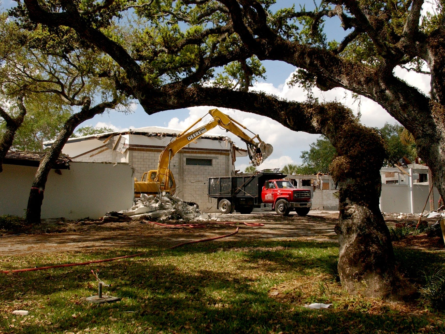 March 14, 2002 - Workers with L.E.B. Demolition of Jensen Beach maneuver to save the trees on the grounds as they demolish buildings at the Riomar Bay Yacht Club in Vero Beach to make way for construction of the Quail Valley Towne Club. The construction was expected to consist of a 12,000-square-foot clubhouse that has a 90-seat pub and grill and a semi-formal dining room with 140 seat indoors and 40 more outdoors.