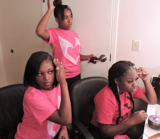 PACE Girl Choir members Rhaniyah, Tylia and Fislande work on their hair and makeup backstage the Sunrise Theatre Black Box in Fort Pierce.