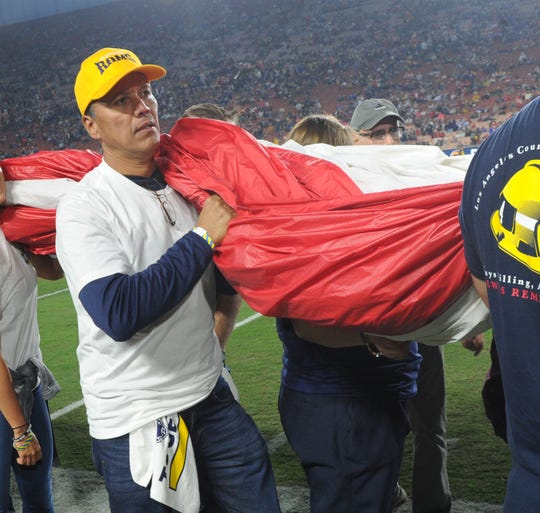 First responder Sgt. Marty Luna, of the Ventura Country Sheriff's Department, helps hold up the American flag during a ceremony before Monday night's game between the Rams and Chiefs at the Coliseum.