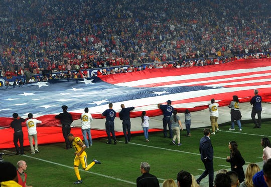 First responders unfurl the American flag before the start of Monday night's game between the Rams and the Chiefs at the Coliseum.