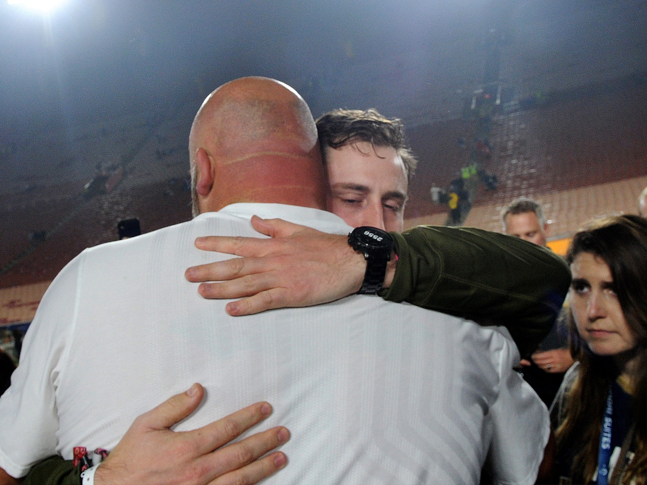 Rams offensive tackle Andrew Whitworth, left, hugs Jordan Helus, son of Ventura County Sheriff's Sgt. Ron Helus, after Monday night's game against the Chiefs. Sgt. Helus was killed during the Borderline Bar & Grill shooting.