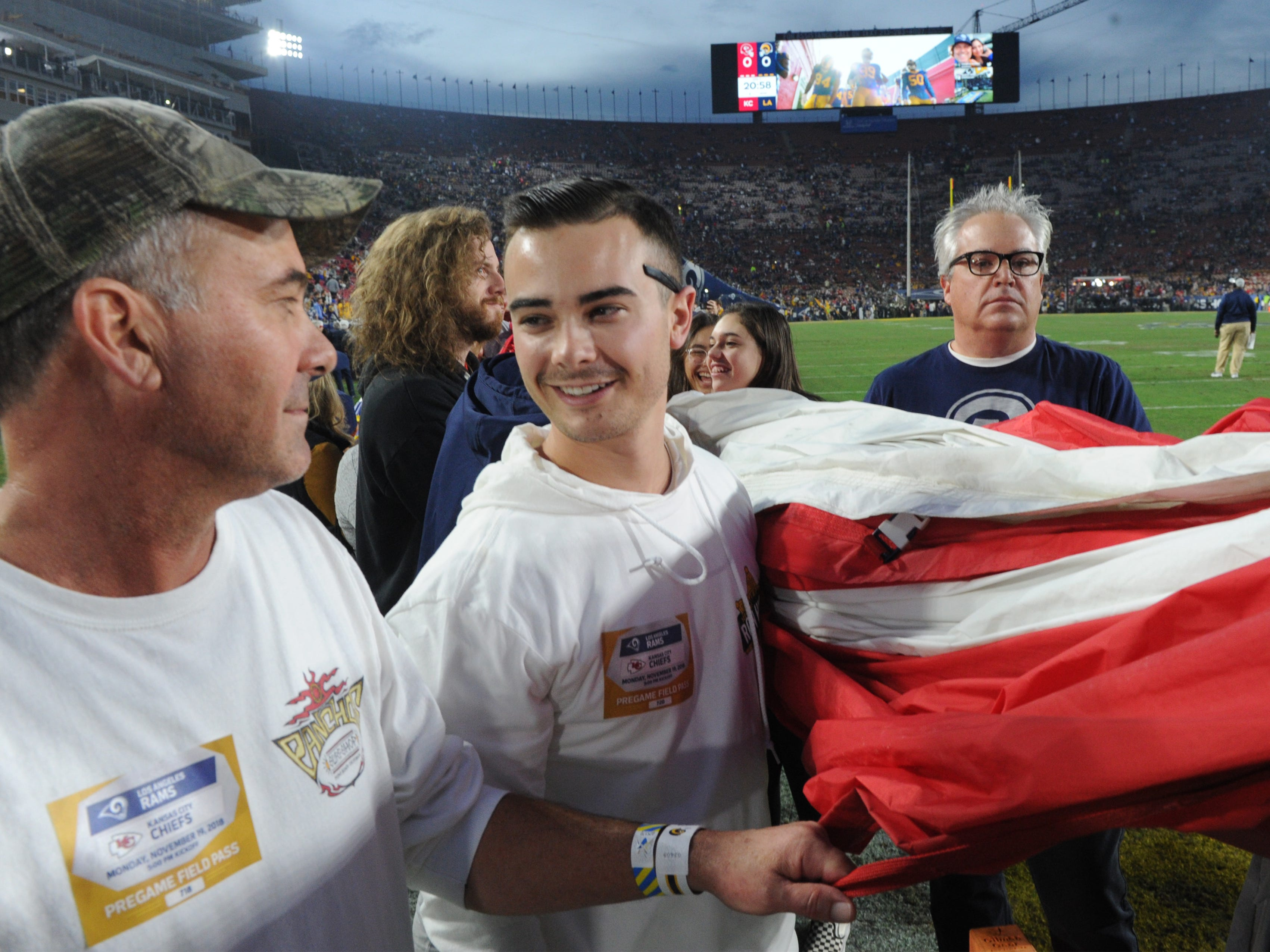 Richard Hain, left, and his son J.T. Hain, who was inside the Borderline Bar & Grill at the time of the mass shooting, participate in the American flag ceremony before Monday night's game between the Rams and Chiefs at the Coliseum.