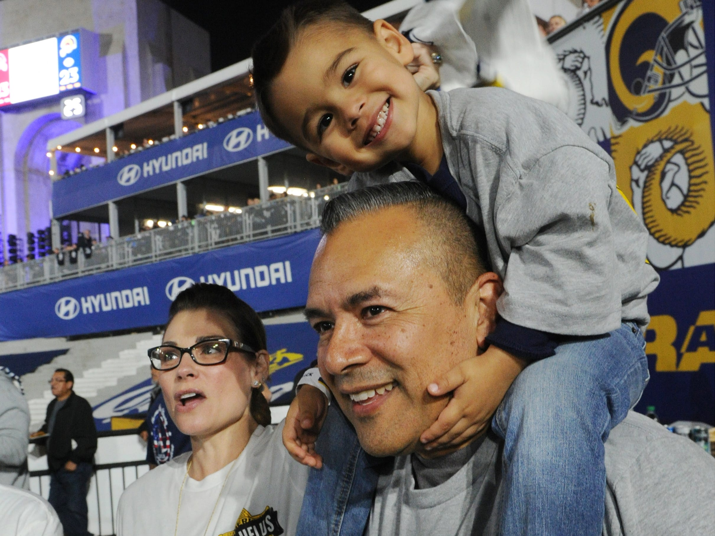 First responder Sgt. Jose Rivera, of Camarillo and the from the Ventura County Sheriff's Department, and his son Kelley, 3, and wife Tristen enjoy Monday night's game between the Rams and the Chiefs at the Coliseum.