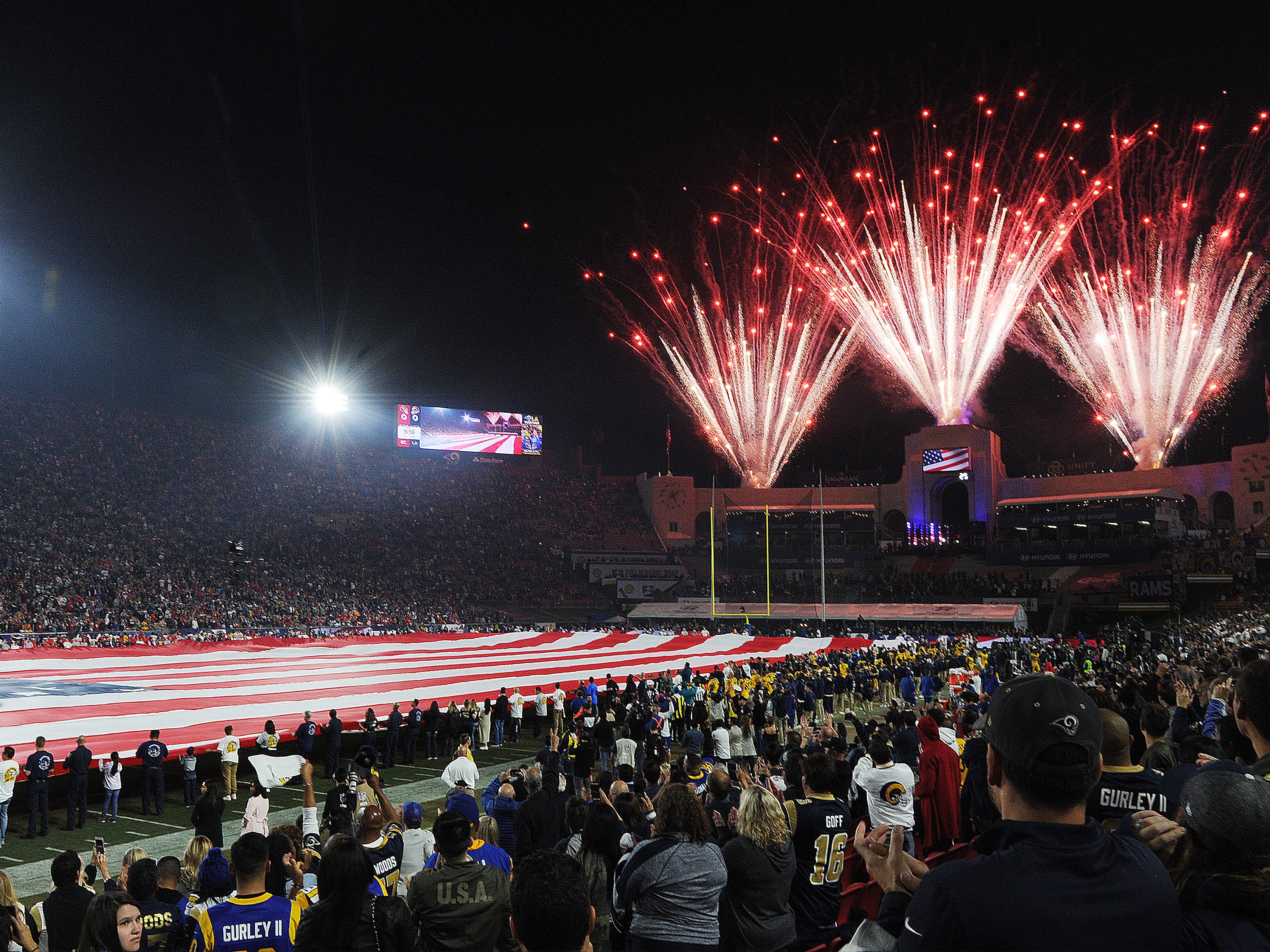 First responders hold the American flag during the national anthem before Monday night's game between the Rams and Chiefs at the Coliseum.