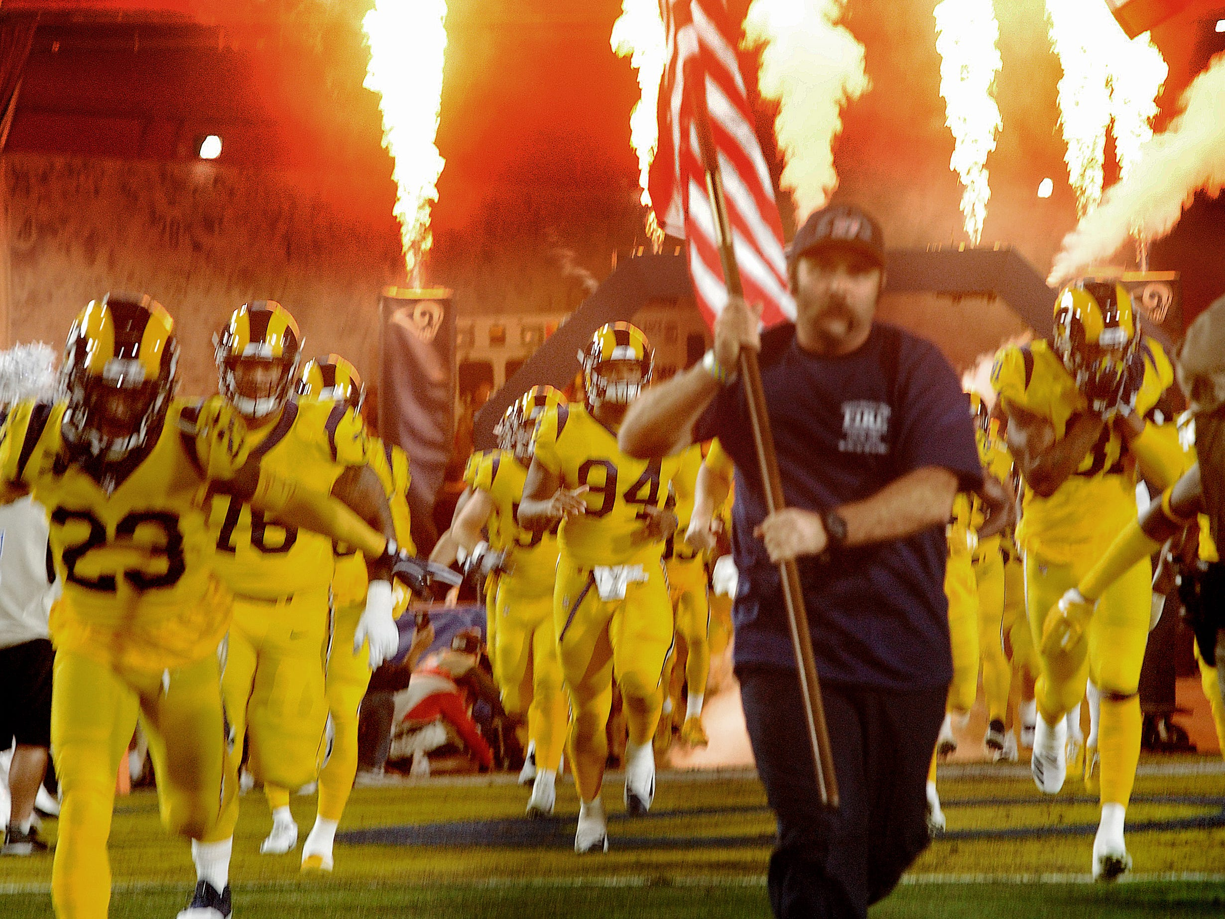 The Rams take the field before Monday night's emotional game against the Chiefs at the Coliseum.