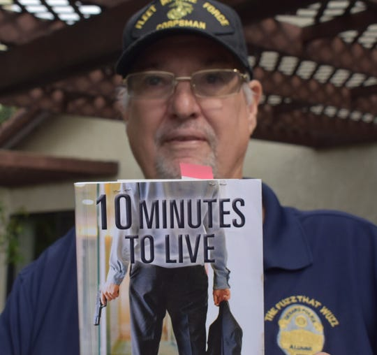 Retired Oxnard Police Department Detective Len Newcomb displays a book from a recent training session he attended on active shooter situations.  Newcomb was one of the officers who chased after gunman Alan Winterbourne 25 years ago on Dec. 2.