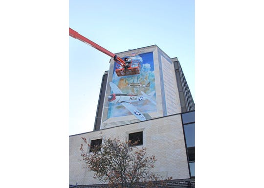 Sam Donovan, a mural artist, restores the Wall of Remembrance mural on the north face of Millville City Hall at High and Main streets.