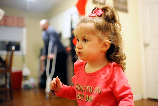 Addilynn Hines, 2, plays in her living room while her dad Charles stands in the background on Friday, November 16, 2018.
