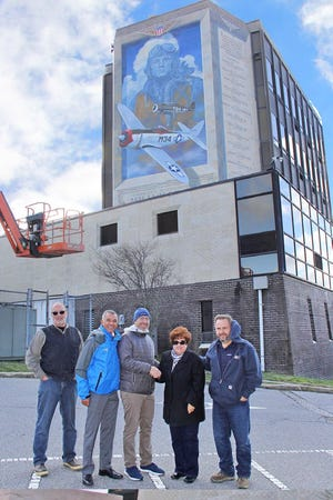 Lisa Jester, executive director, Millville Army Air Field Museum (second right), thanks Matthew Pisarski, assistant planning director, Cumberland County, (center), and John Ruga, president, Northeast Precast (right), for their assistance with the restoration of the Wall of Remembrance mural on the north face of Millville City Hall on High and Main streets. The mural commemorates the World War II history of the Millville Air Base at Millville Airport, America's First Defense Airport. Also pictured are mural artist Sam Donovan (left) and Millville Mayor Michael Santiago (second left).