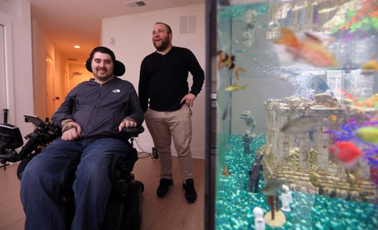 Tommy McGuire looks at his fish tank in his Haverstraw home with his friend Ryan Leonard of Bardonia Nov. 20, 2018. McGuire continues to recover from a spinal injury after a swimming accident. The annual Tommy Turkey bowl fundraiser will be held Nov. 24 at Clarkstown South High School.