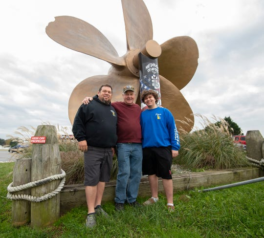Three generations of the Meding family, Robbie Meding (left), Henry Meding and Dayton Meding stand outside of Meding's Seafood in Milford near the landmark ship's propeller.
