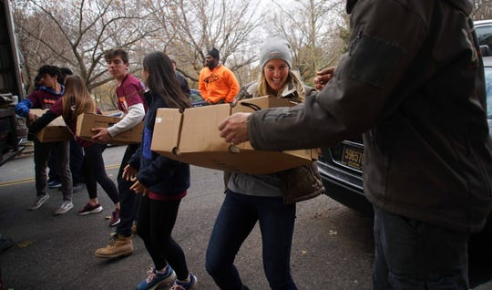 Volunteers help unload turkeys at Baynard Apartments, one of Norman Oliver's stops on his turkey giveaway to assist families and seniors. This year's turkey goal was to provide more than 6,000 families with turkeys.