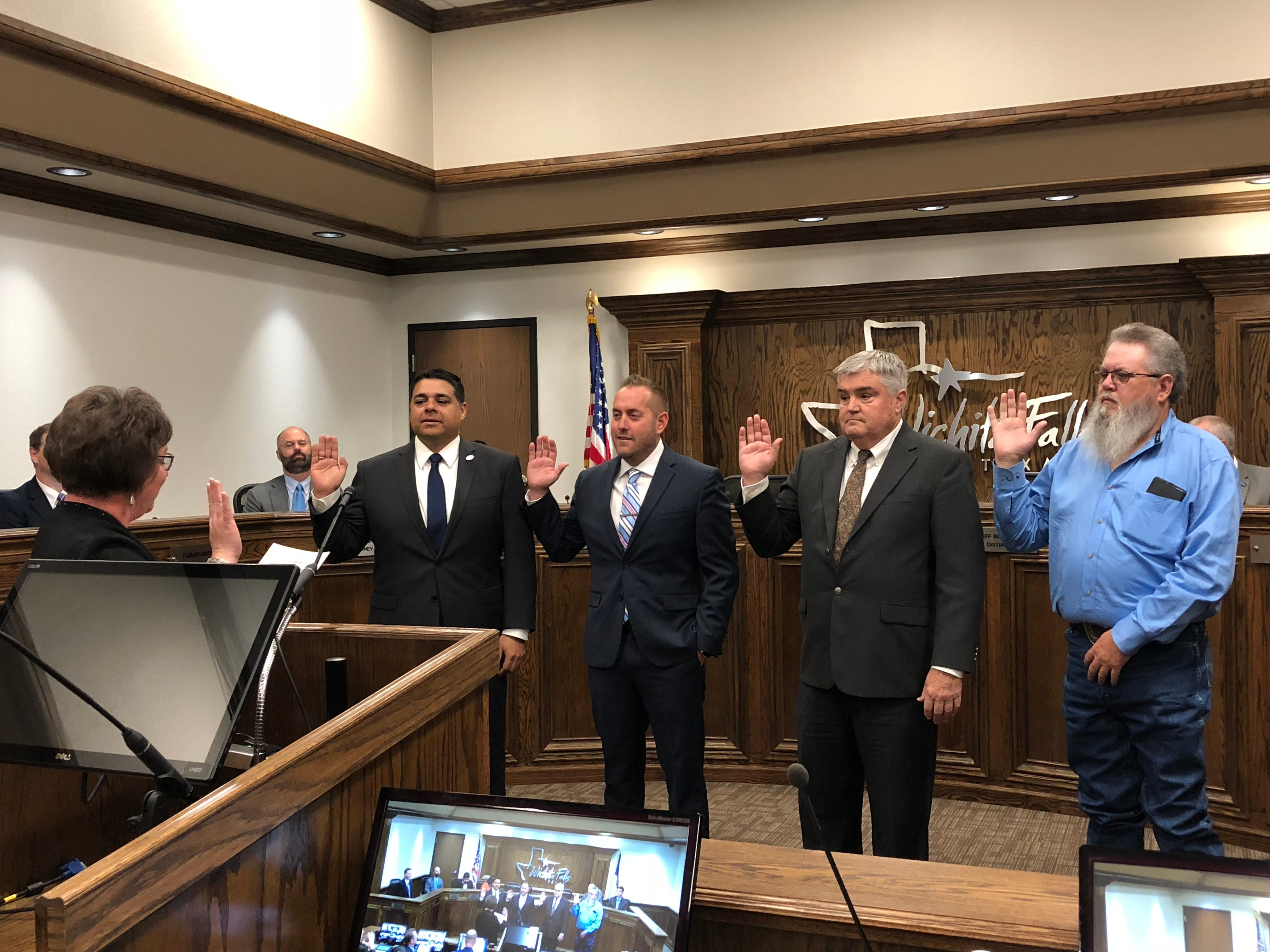 Newly elected and re-elected city officials talk the oath of office with Marie Balthrop, city clerk, left, on Tuesday. From left are Mayor Stephen Santellana, Jeff Browning, Tim Brewer, and Steve Jackson.