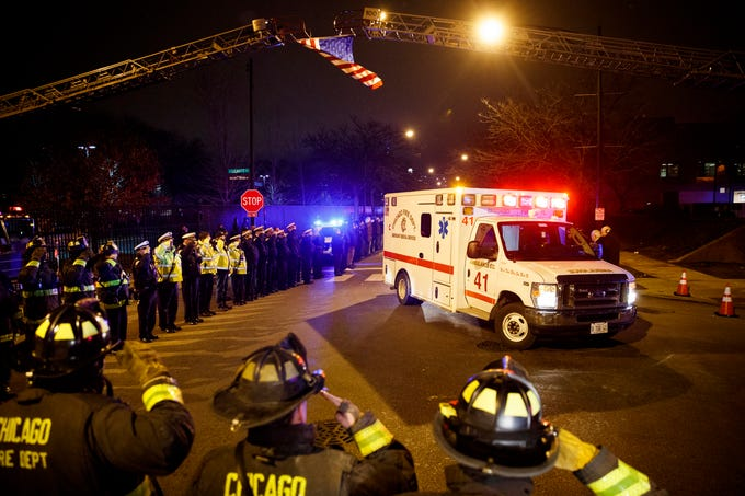 Police and firefighters salute as an ambulance arrives at the medical examiner's office carrying the body of Chicago Police officer Samuel Jimenez, who was killed during a shooting at Mercy Hospital earlier in the day, Monday, Nov. 19, 2018, in Chicago.