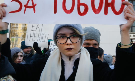 """A young woman attends a gay and lesbian rally a few days before the International Transgender Day of Remembrance in Kiev, Ukraine, Sunday, Nov. 18, 2018. Writing on the poster reads: """"If you stay silent, they will come for you, too."""" The day is observed annually in Ukraine to memorialize those who have been murdered as a result of transphobia. Amnesty International in Ukraine has warned on the growing violence against sexual minorities from radical groups."""