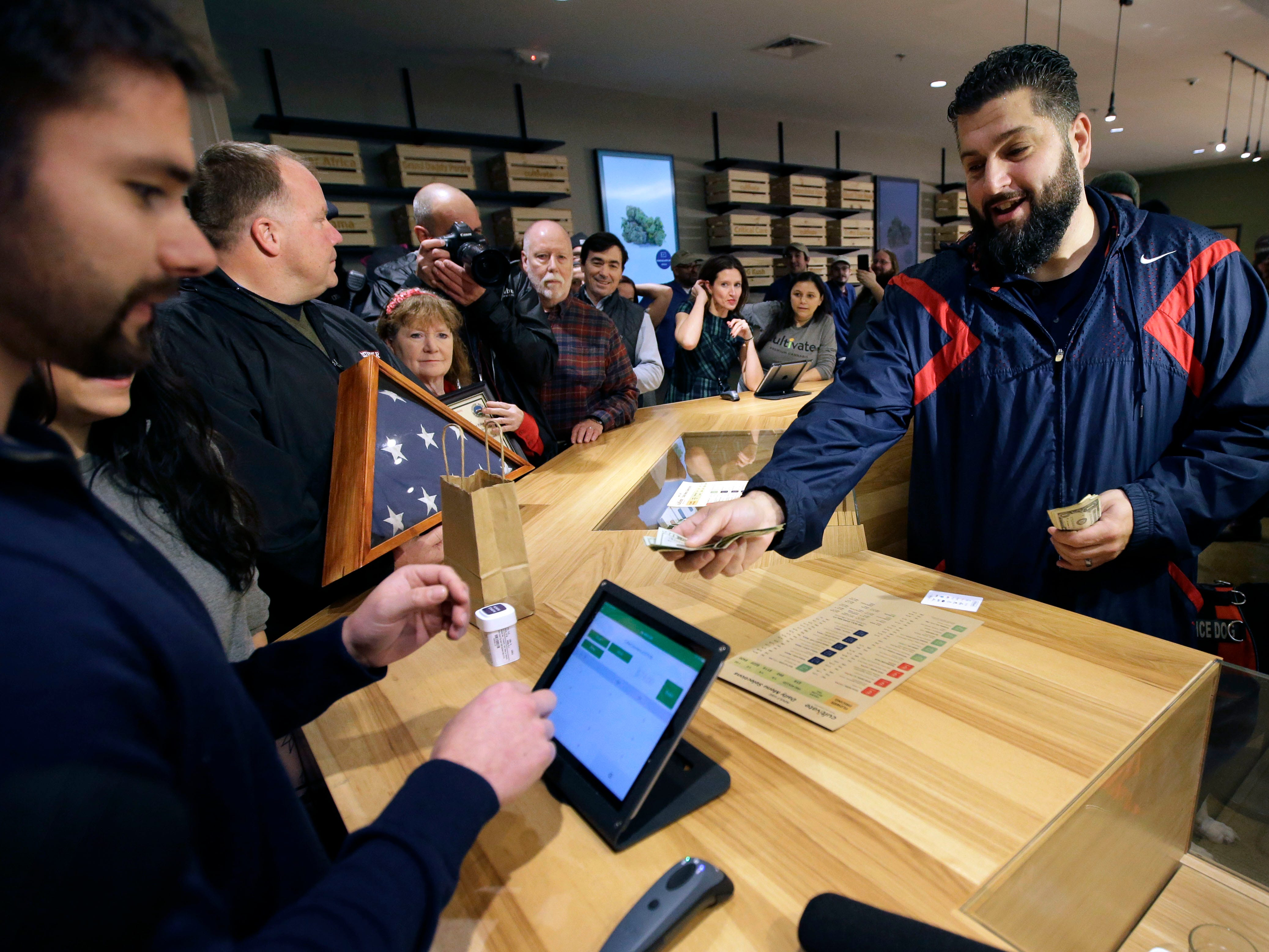 Stephen Mandile, right, an Iraq War veteran from Uxbridge, Mass., is the first to purchase recreational marijuana at the Cultivate dispensary on the first day of legal sales, Tuesday, Nov. 20, 2018, in Leicester, Mass. Cultivate is one of the first two shops permitted to sell recreational marijuana in the eastern United States, more than two years after Massachusetts voters approved it in 2016.