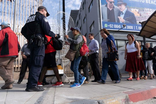 U.S. Customs and Border Protection officers check the IDs of pedestrians crossing into the United States after reopening the San Ysidro port of entry on Nov.19, 2018, in Tijuana, Mexico.