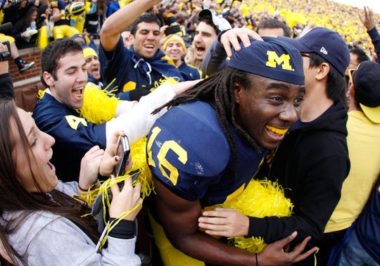 Denard Robinson of the Michigan Wolverines celebrates with students after beating Ohio State 40-34 at Michigan Stadium on Nov. 26, 2011 in Ann Arbor.
