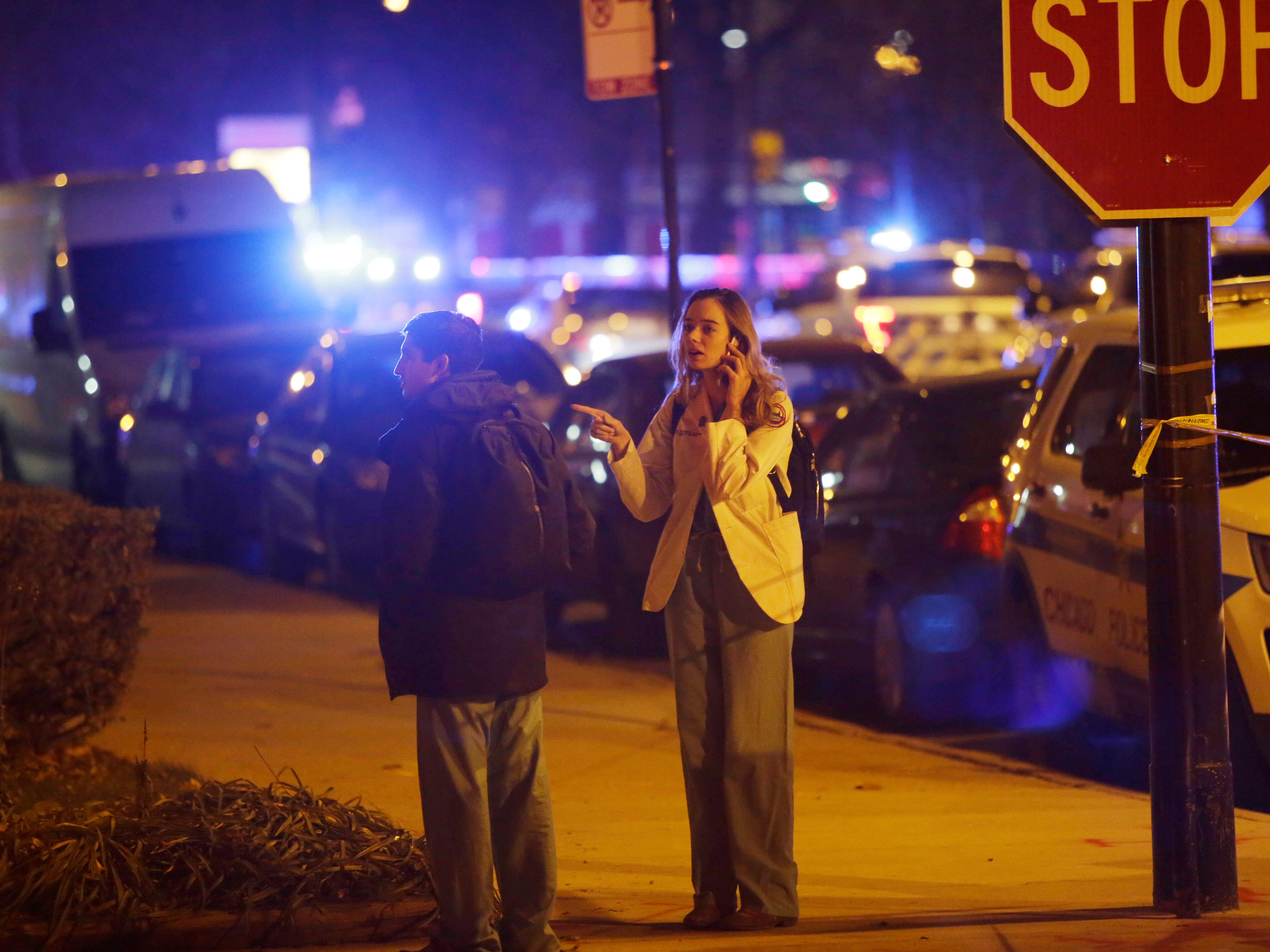 Mercy Hospital workers stand outside the hospital after a gunman shot multiple people on Nov. 19, 2018 in Chicago.