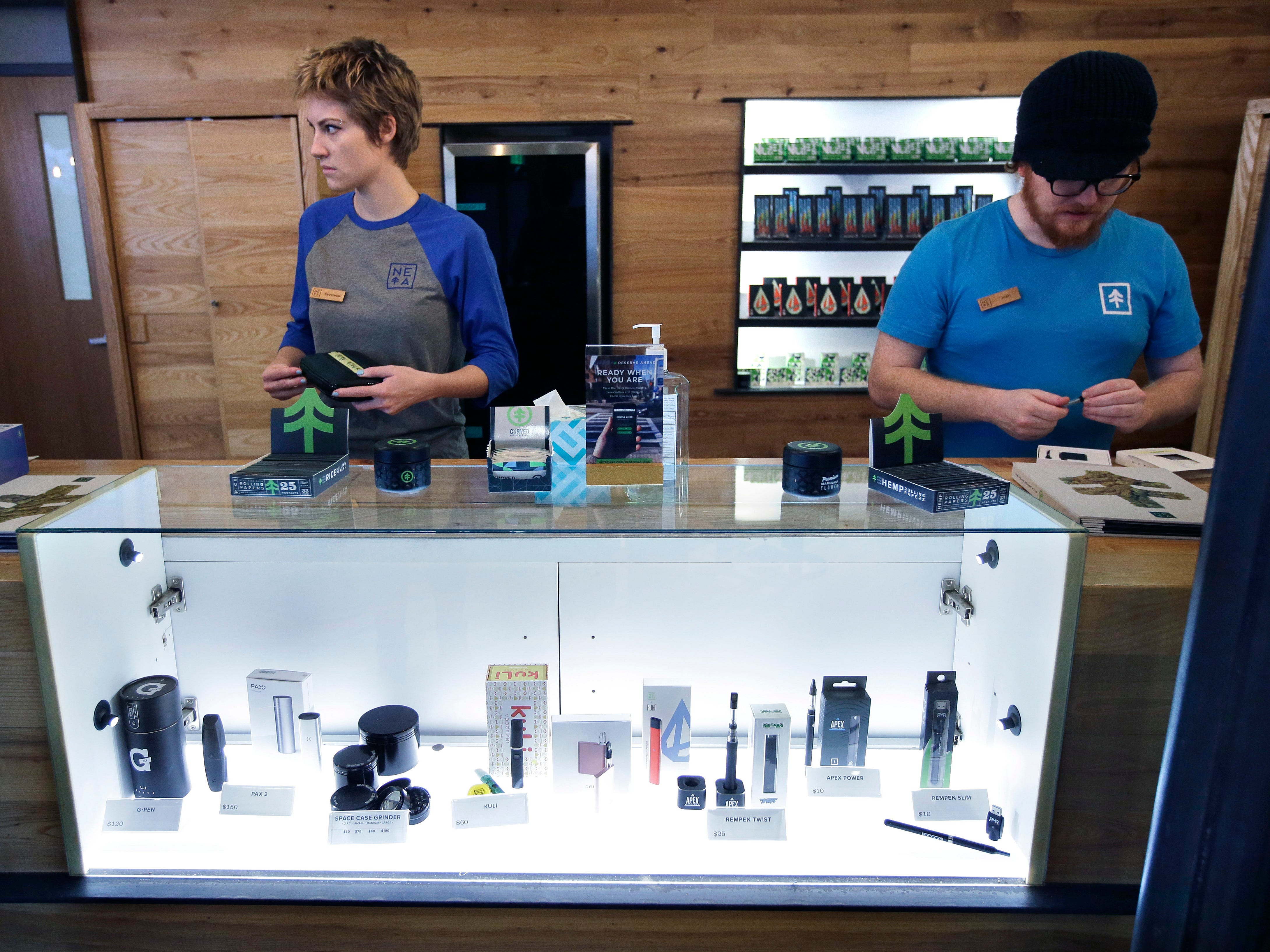 Patient service associates Savannah Stuitje, left, and Josh Hirst, right, stand at a counter that features a display of vape dispensers, below, that could be used for legal recreational cannabis, at New England Treatment Access medical marijuana dispensary, in Northampton, Mass, Oct. 17, 2018. New England Treatment Access, and another store in Leicester, Mass., have been given the green light to begin selling recreational pot on Tuesday, Nov. 20, making them the first commercial pot shops in the eastern United States.
