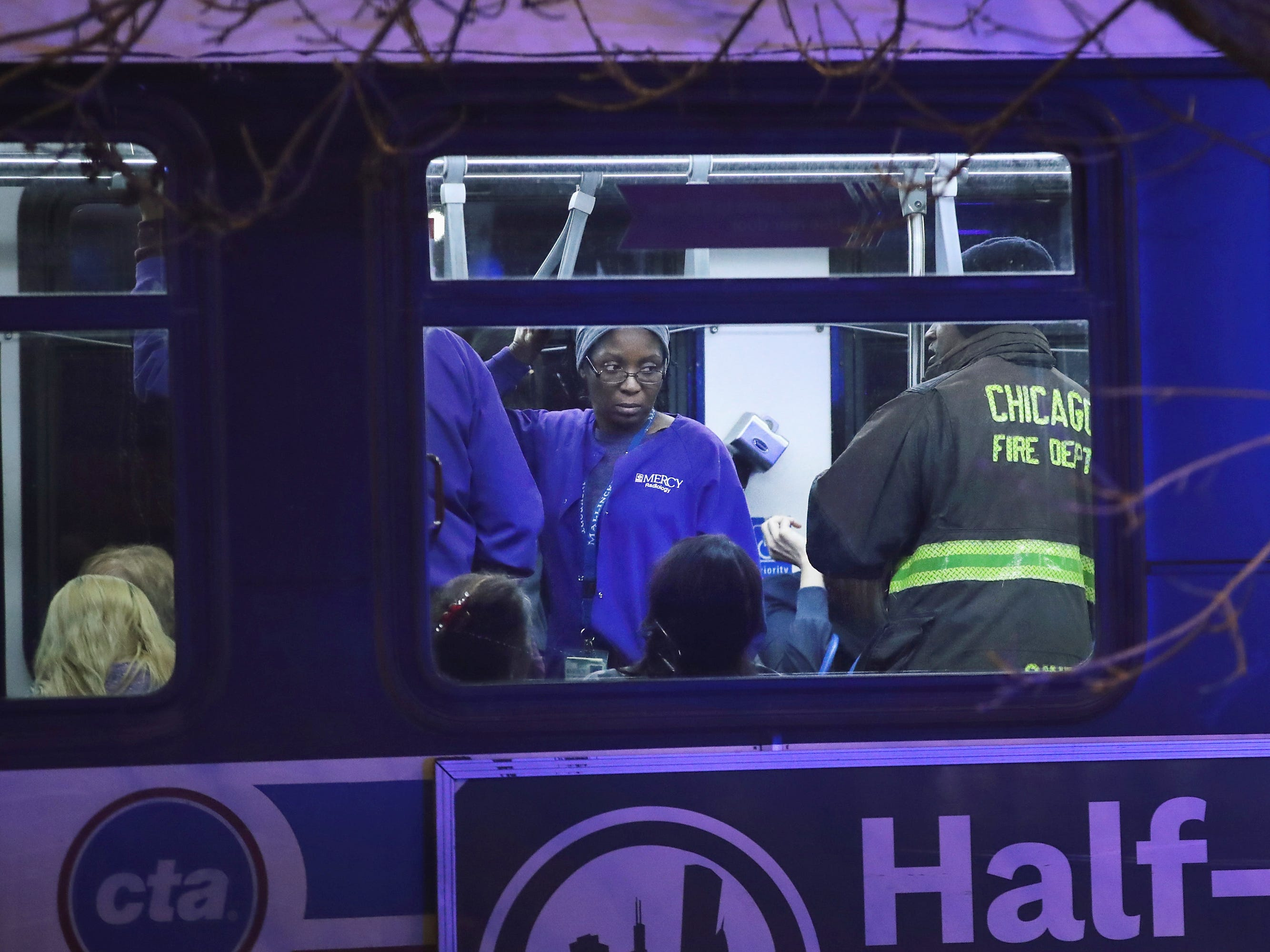 People believed to be Mercy Hospital workers wait on city buses outside after a gunman opened fire at Mercy Hospital on Nov. 19, 2018 in Chicago.