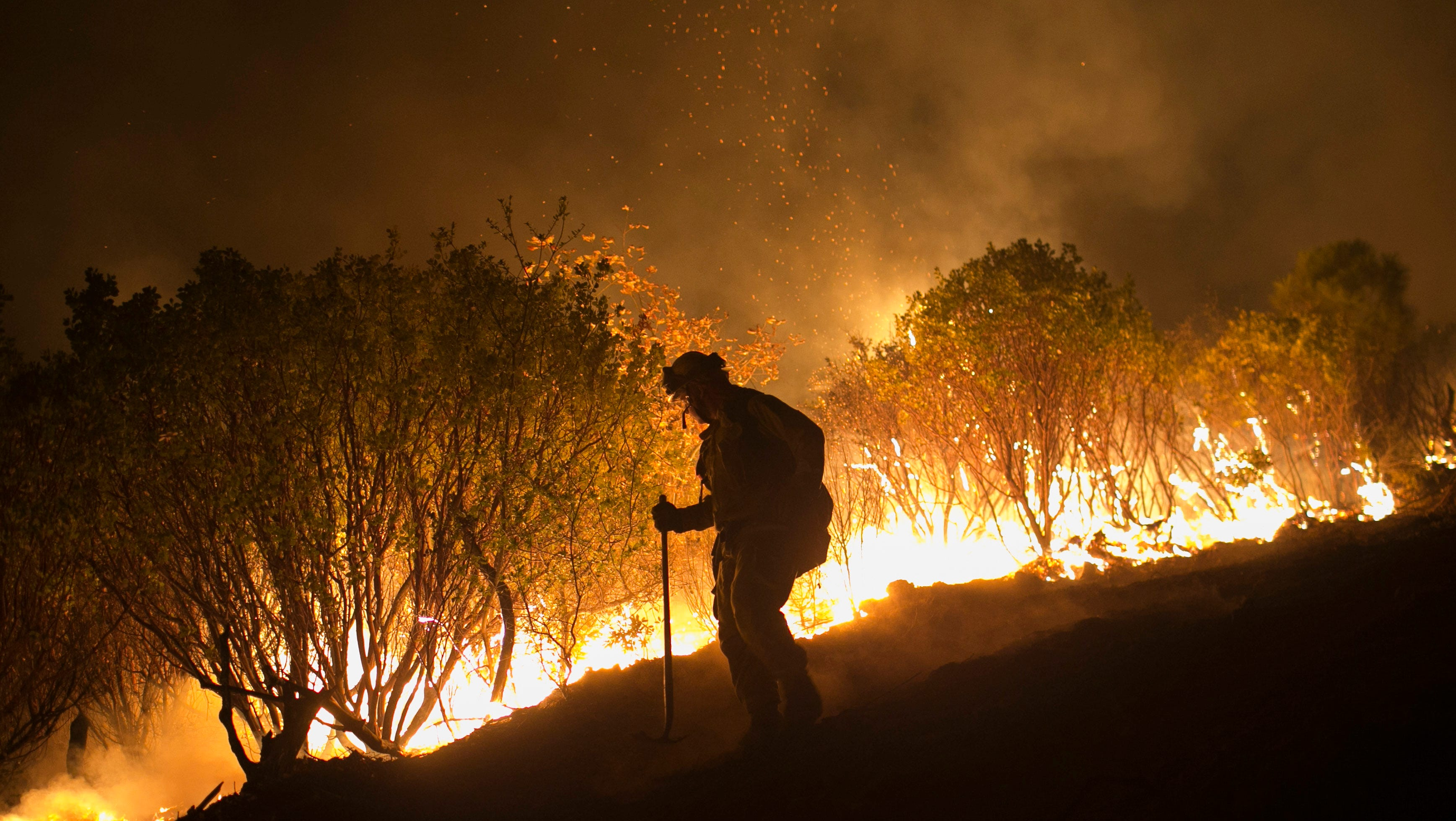 Nov. 14, 2018; Butte County, CA, USA; Firefighters hold a line in the Camp Fire with a control burn near Bloomer Hill in Butte County in California. Mandatory Credit: Thomas Hawthorne/The Arizona Republic via USA TODAY NETWORK ORIG FILE ID: 20181115_ajw_usa_006.jpg