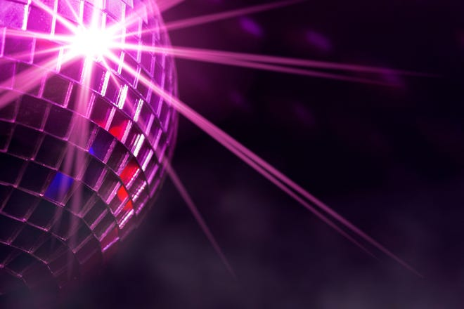 Retro disco ball with violet star burst reflections and fog in club