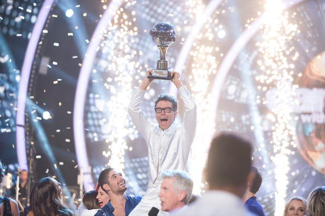 "Bobby Bones hoists the mirrorball trophy on ""Dancing With the Stars."""